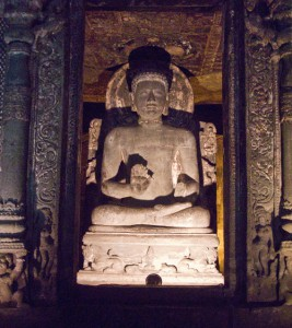 Large seated Buddha in a small room, carved from solid rock at Ajanta caves.