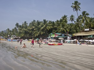 Sunbathers, beach walkers and restaurants line Palolem Beach, Goa, India.