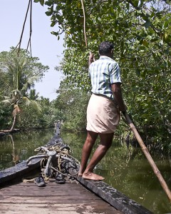 A boatman pushes a houseboat along a backwater canal in Kerala.