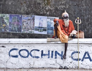 A Sadhu rests on a wall in Cochin.